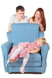 Girl is lying on char, parents behind her Royalty Free Stock Photos