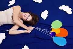 Girl lying on the clouds with baloons Royalty Free Stock Photos