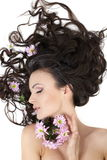 Girl lying with colorful flowers in her hair Stock Photography