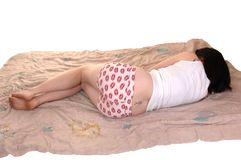 Girl lying on comforter. Stock Photos