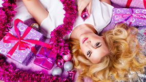 Girl lying on the couch. Around gifts and festive tinsel. Royalty Free Stock Image