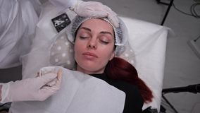 The girl is lying on the couch, the beautician corrects her hat, the girls are preparing for permanent makeup. 4K Slow. The girl is lying on the couch, the stock video footage