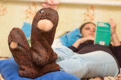 The girl is lying on couch and is reading a book, in the foreground the holey socks Stock Photos