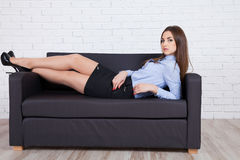 Girl lying on a couch and stares into the camera Royalty Free Stock Photography