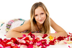 Girl lying in covered by flower petals Royalty Free Stock Image