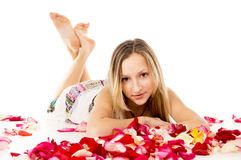 Girl lying in covered by flower petals Stock Photo