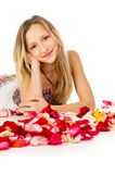 Girl lying in covered by flower petals Royalty Free Stock Photo