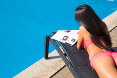 Girl lying on deckchair and reading magazine stock images
