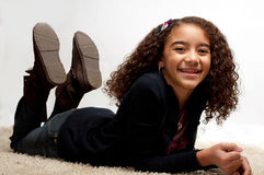 Girl lying down with a big smile. Young girl lying down with a big smile. She is 10 to 15 years old, dark skinned, curly haired, and appears to be very happy Royalty Free Stock Photo