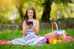 Girl lying down on blanket and using tablet Stock Photos