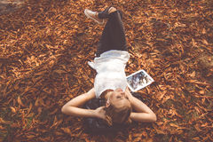 Girl is lying down with digital tablet outdoor Stock Photography