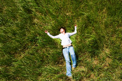 Girl lying down of grass Stock Photos