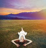 Girl lying down at green grass meadow with sunrise. Young redhead girl lying down at green grass meadow with sunrise over mountines in summer time Royalty Free Stock Photos