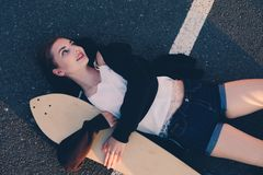 Girl lying down with her longboard on asphalt road and looking away Stock Images