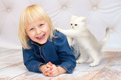 Girl lying down and laughing. Kitten pushing her shoulder Royalty Free Stock Photos