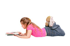 Girl lying down reading. Young caucasian girl lying down reading a book isolated on white Royalty Free Stock Photo