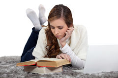 Girl lying down reading Stock Photo