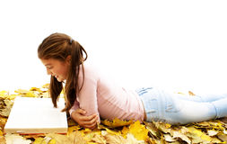 Girl lying down reading book with leaves around Stock Images