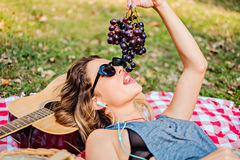Girl lying and eating grapes in the park Stock Images