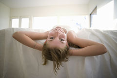 Girl (11-13) lying at edge of bed with hands behind head, smiling, rear view, portrait stock image