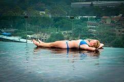Girl Lying on Edge of Infinity Pool Royalty Free Stock Images