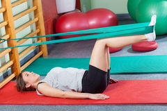 Girl lying on exercise mat and stretching legs Royalty Free Stock Images