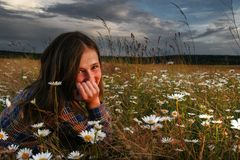 Girl lying in field of daisies. Attractive teenage girl lying in field of chamomile or daisy flowers with dramatic, dark cloudscape background royalty free stock images