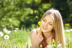 Girl lying on the field of dandelions Stock Photo