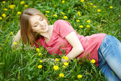 Girl lying on the field of dandelions Royalty Free Stock Images