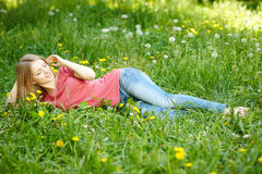 Girl lying on the field of dandelions Stock Image