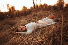 Girl lying on the field on a sunset background Royalty Free Stock Photos