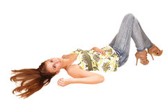 Girl lying on floor. A beautiful woman in jeans and blouse, with long brunette hair lying on her back on the floor, having a good time, for white background stock image