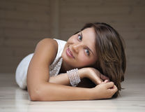 Girl lying on the floor. And smiling Stock Image