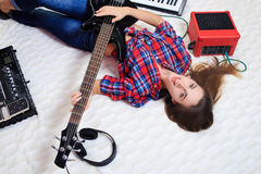 Girl lying on the floor with bass guitar Royalty Free Stock Photos