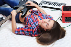 Girl lying on the floor with bass guitar Royalty Free Stock Image