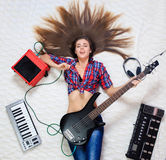 Girl lying on the floor with bass guitar. And speaker royalty free stock photos
