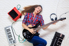 Girl lying on the floor with bass guitar Stock Photos
