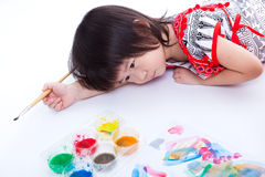 Girl lying on floor and hold paintbrush. On white. Studio shot Stock Photos