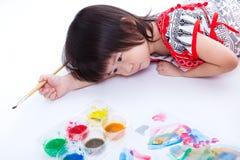 Girl lying on floor and hold paintbrush. On white. Studio shot Stock Photos