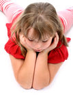 Girl lying on floor looking down at something Stock Images