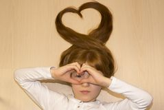Girl with hearts from her hands and hair. Girl lying on the floor and making hearts from her hands and hair Stock Image