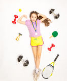 Girl lying on floor with set of sport equipment Stock Photography