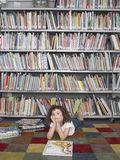 Girl Lying On Floor With Storybook In Library stock photography
