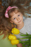Girl lying on the floor with tulips as a present for mother Royalty Free Stock Images