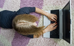 Girl lying on the floor and using her notebook. Girl lying on the floor and using her laptop. Top view Royalty Free Stock Photo