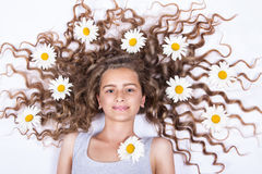 Girl lying with flowers in her hair Stock Image