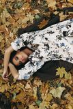 Girl lying in foliage royalty free stock image