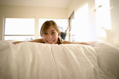 Girl (11-13) lying on front on bed, smiling, portrait, low angle view Royalty Free Stock Photo