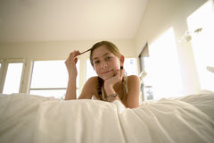 Girl (11-13) lying on front on bed, twirling hair in fingers, hand on chin, smiling, portrait, low angle view Royalty Free Stock Photography