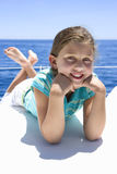 Girl (8-10) lying on front on deck of sailing boat out at sea, smiling, portrait Stock Photo